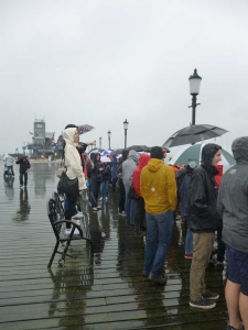 Photograph of spectators, with umbrellas and raincoats, at the end of Southend Pier.